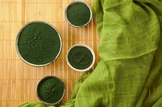 Spirulina algas, spirulina em pó em copos de cerâmica Foto Premium