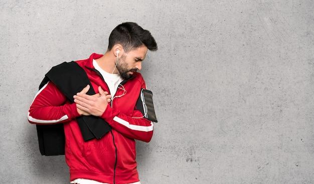 Sportman bonito tendo uma dor no coração sobre parede texturizada Foto Premium