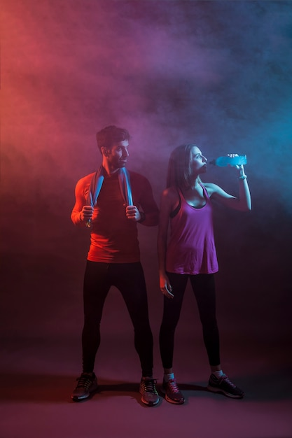 Sportspeople in dark studio após treinamento Foto gratuita