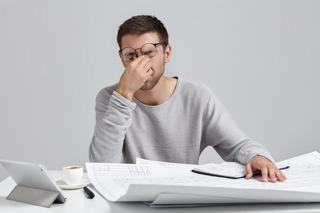 Stess, excesso de trabalho e prazo. jovem arquiteto freelancer com a barba por fazer cansado massageando a ponte do nariz Foto gratuita