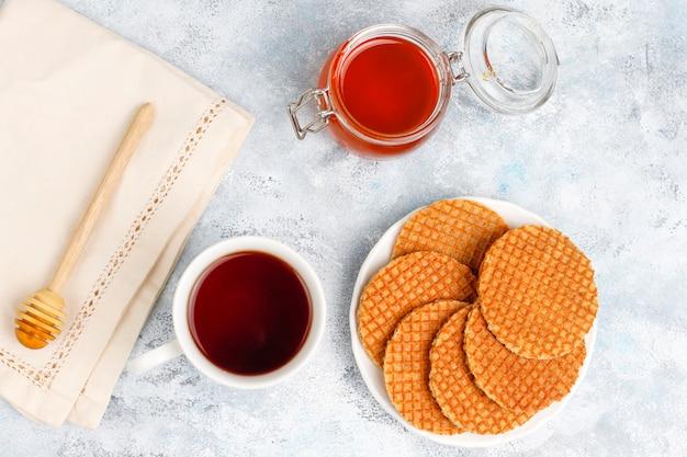 Stroopwafels, waffles holandeses de caramelo com chá ou café e mel no concreto Foto gratuita