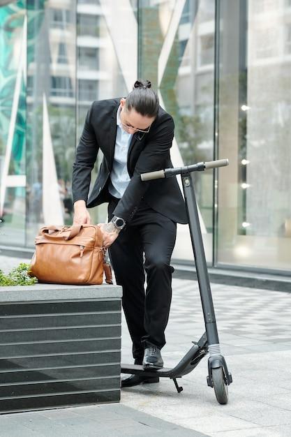 Stylidh jovem empresário com scooter procurando um documento em uma bolsa de couro enquanto fala ao telefone com um colega Foto Premium