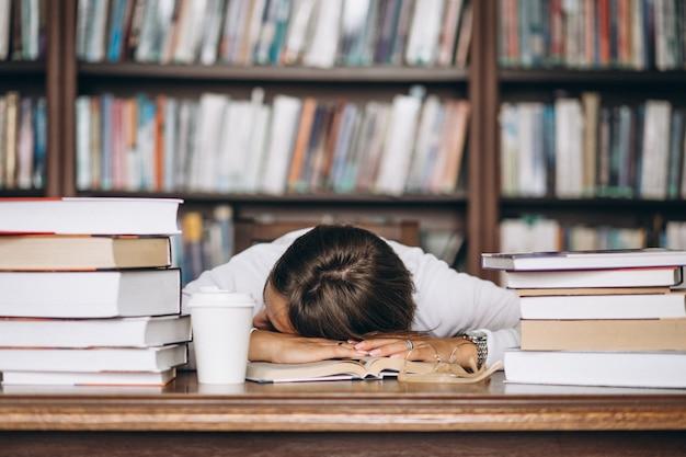 Súbito dormindo na biblioteca em cima da mesa Foto gratuita