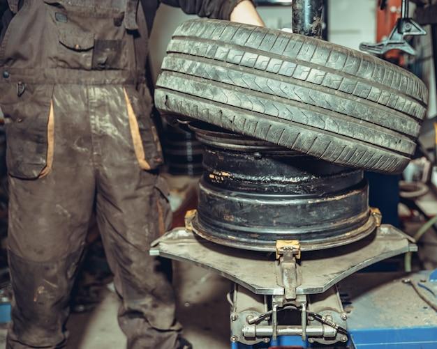 Substituição de pneus nas rodas do carro em serviço Foto Premium