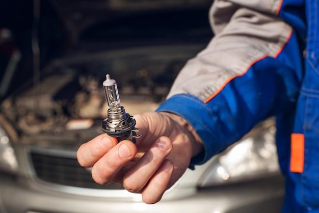 Substituindo uma lâmpada queimada no farol do carro Foto Premium