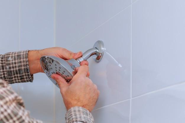 Substituir o encanamento no banheiro chuveiro montado mão com altura ajustável um chuveiro. Foto Premium