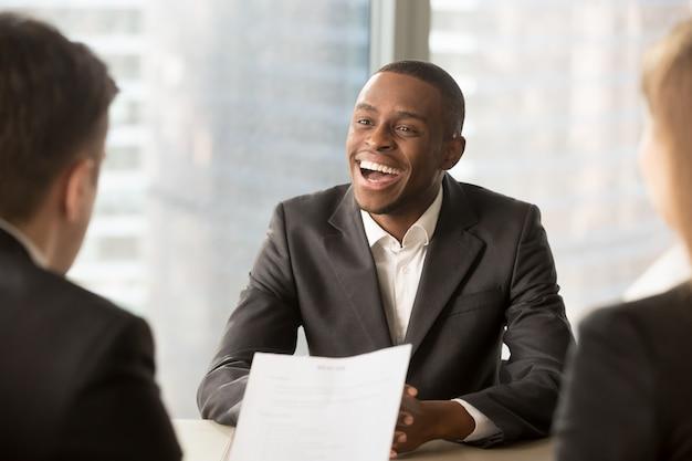Sucesso feliz candidato masculino preto sendo contratado, conseguiu um emprego Foto gratuita