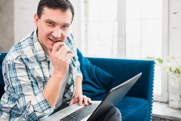 Sucesso masculino usando laptop no sofá em casa Foto gratuita