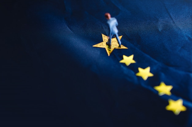 Sucesso no negócio ou no conceito do talento. vista superior, de, um, miniatura, homem negócios fica, ligado, um, amarela, estrela dourada Foto Premium