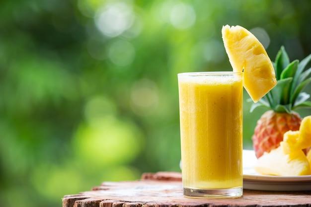 Suco de abacaxi com pedaços de abacaxi cru Foto gratuita