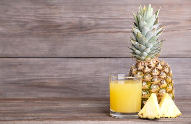 Suco de abacaxi fresco no copo com fatias Foto Premium