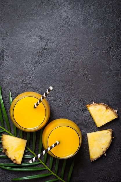 Suco de abacaxi ou smoothies e fatias de abacaxi em um fundo preto Foto Premium
