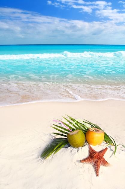 Suco de coquetéis de coco e estrela do mar na praia tropical Foto Premium
