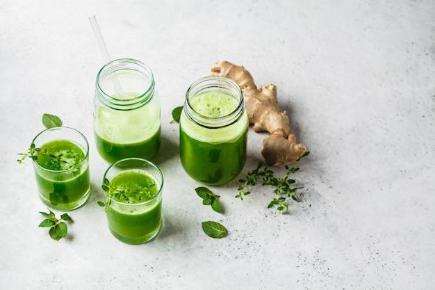 Suco de desintoxicação verde com gengibre e hortelã em copos e potes Foto Premium