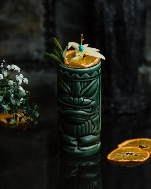 Suco de laranja com fatias de frutas em uma jarra verde étnica Foto gratuita