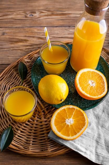 Suco de laranja de alto ângulo em garrafa e copo Foto gratuita