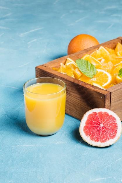 Suco de laranja e fatias de frutas frescas Foto gratuita