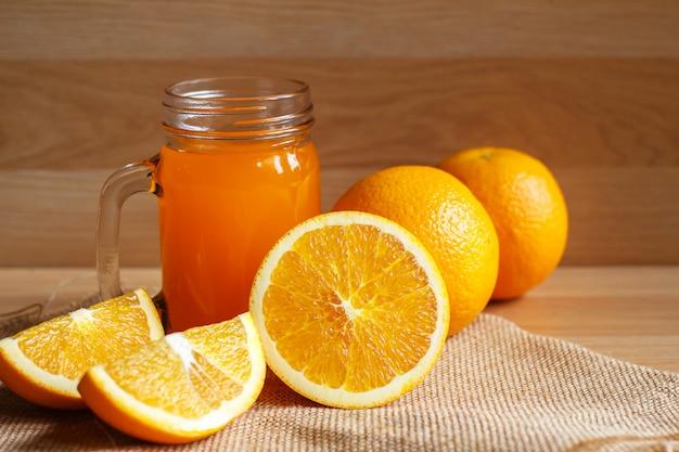 Suco de laranja e laranja em fundo de madeira Foto Premium