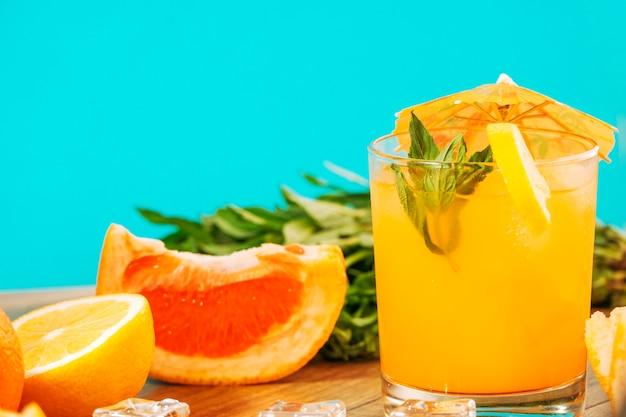Suco de laranja e pedaços de frutas cítricas Foto gratuita
