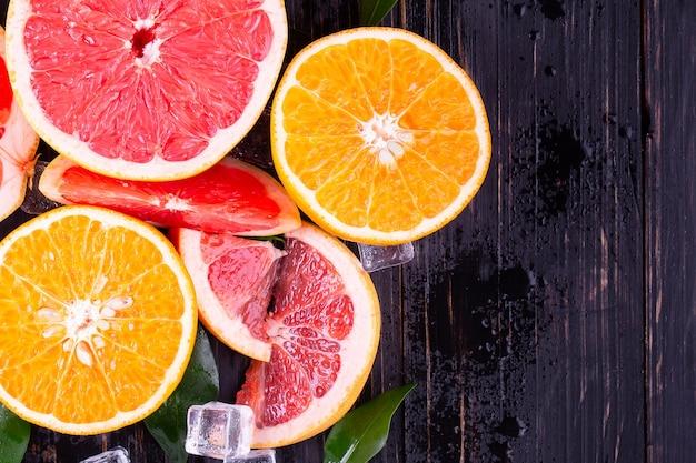 Suco de laranja e toranja em um fundo preto de madeira Foto Premium