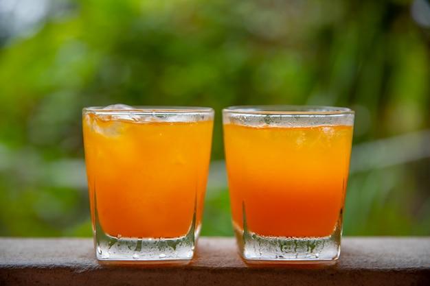 Suco de laranja em 2 folhas em um fundo natural. Foto Premium