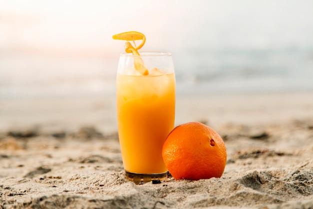 Suco de laranja em pé na areia Foto gratuita
