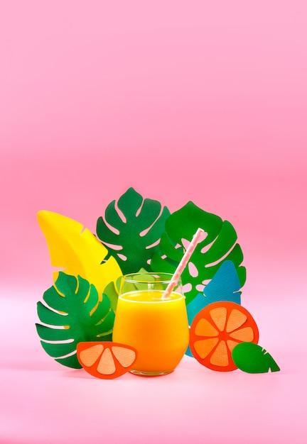 Suco de laranja em uma grama com folhas de papel e laranja no lado. conceito tropical foco seletivo. Foto Premium