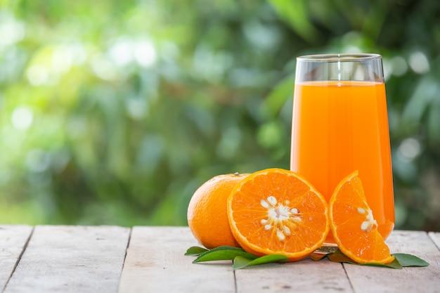 Suco de laranja em uma jarra com laranjas Foto gratuita