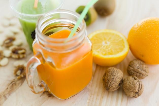Suco de laranja em vidro, nozes e frutas frescas em madeira backgroun Foto gratuita