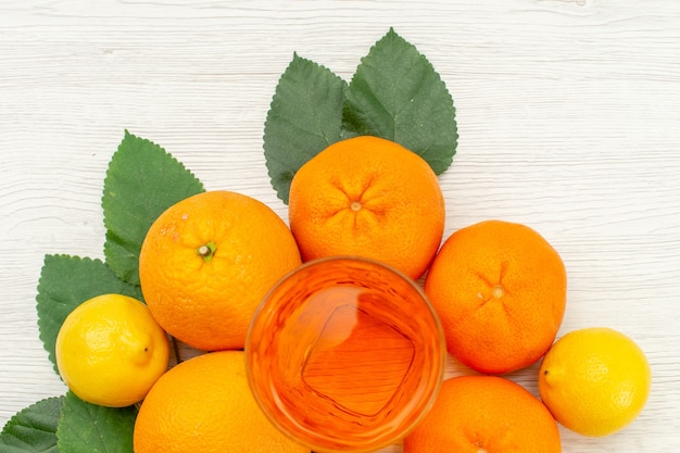 Suco de laranja fresco com laranja e frutas cítricas em uma superfície branca clara suco de frutas tropicais cítricas Foto gratuita
