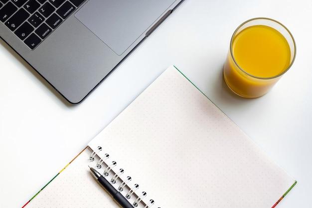 Suco de laranja no local de trabalho. portátil, vidro do suco de laranja e caderno na mesa branca. Foto Premium
