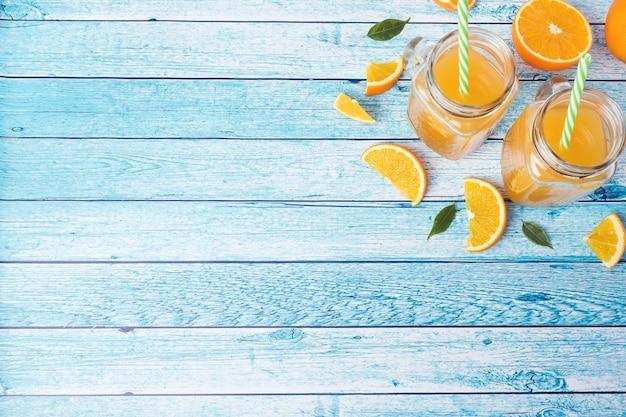 Suco de laranja nos frascos de vidro e laranjas frescas em um fundo azul. Foto Premium
