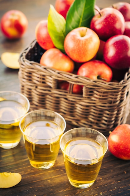 Suco de maçãs em vidro com maçã no cesto Foto gratuita