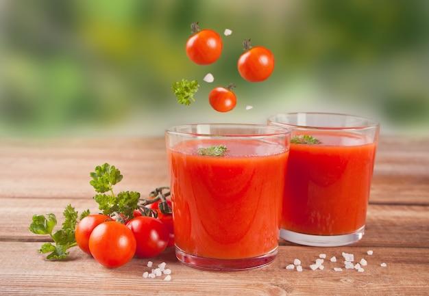 Suco de tomate com salsa na mesa de madeira e voando tomates cereja Foto Premium