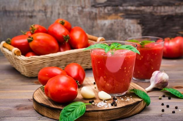 Suco de tomate fresco com folhas de manjericão em copos e tomates em uma mesa de madeira Foto Premium