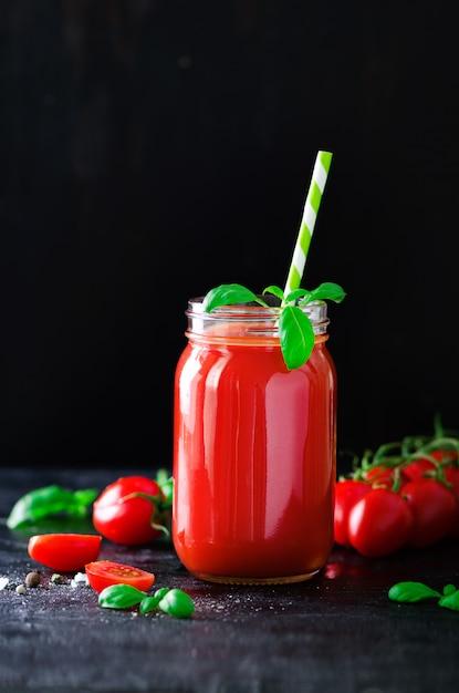 Suco de tomate fresco orgânico em um frasco de vidro, manjericão, cereja, sal, pimenta e palha em preto escuro. limpar comer e dieta conceito. espaço da cópia Foto Premium