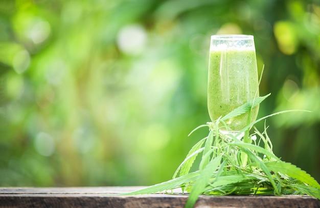 Suco de verão com smoothies de frutas verdes em vidro com planta de maconha de folha de cannabis na madeira Foto Premium