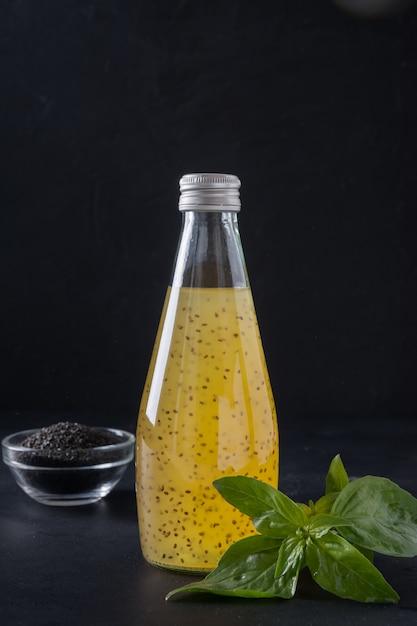 Suco tropical laranja com sementes de manjericão em garrafa no preto. fechar-se. Foto Premium