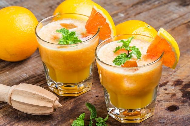 Sucos de laranja com um squeezer Foto gratuita