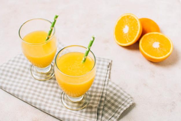 Sucos de laranja frescos de alto ângulo em pano Foto gratuita