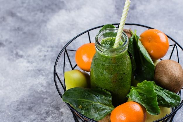 Sucos verdes ou smoothies com kiwi, espinafre, maçã verde, amêndoa cítrica e porca na cesta de metal Foto Premium