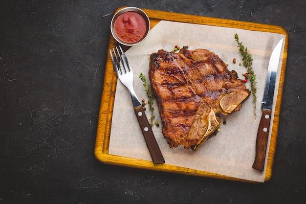 Suculento grelhado grande bife t-bone guarnecido com ervas e sal Foto Premium