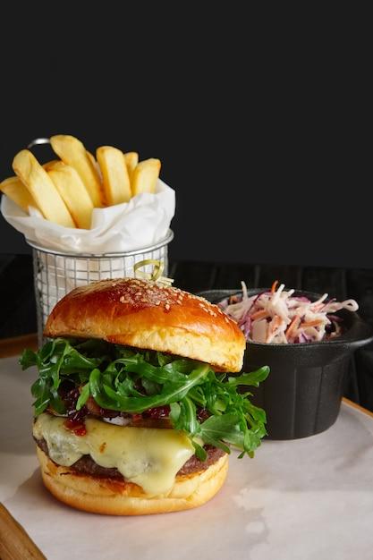 Suculento hambúrguer de carne com molho de lingonberry, queijo derretido, rúcula servido com batata frita e repolho roxo Foto Premium