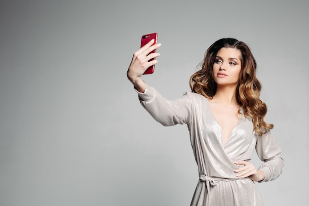Sudactive modelo feminino em prata vestido tirando foto no smartphone. Foto Premium