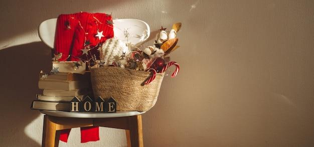 Suéter de inverno colocado em uma cadeira com uma cesta de enfeites de natal Foto Premium