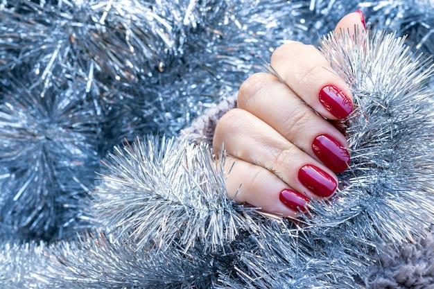 Suéter de malha tricotado com unhas cereja no fundo de uma guirlanda de enfeites de natal prata Foto Premium