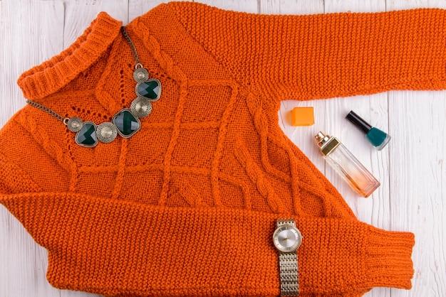 Suéter laranja com acessórios e cosméticos. roupa feminina em fundo de madeira Foto Premium