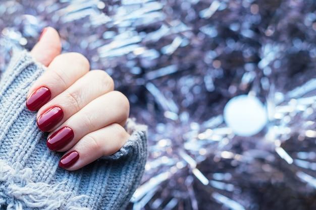 Suéter tricotado à mão com unhas bordô em fundo de guirlanda de enfeites de natal rosa claro Foto Premium
