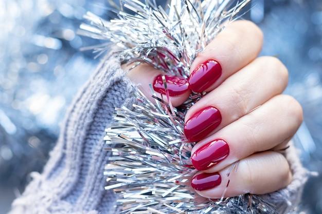 Suéter tricotado à mão com unhas vermelho-escuras Foto Premium