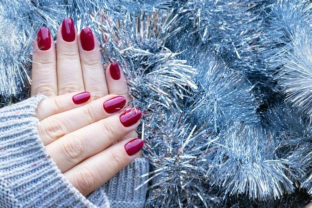 Suéter tricotado com as mãos e unhas bordô em fundo de guirlanda de enfeites de natal prata Foto Premium